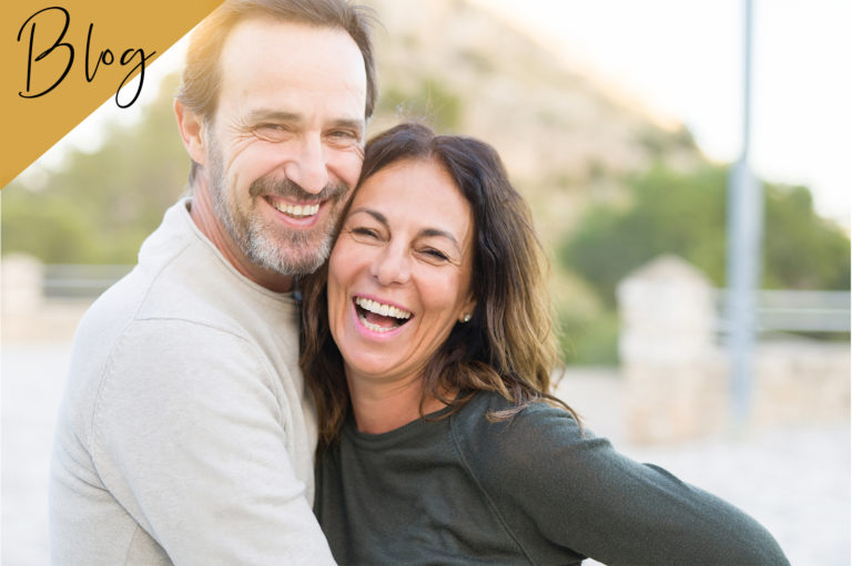 Paar lächelt strahlend in die Kamera und fühlt sich glücklich und erfrischt.