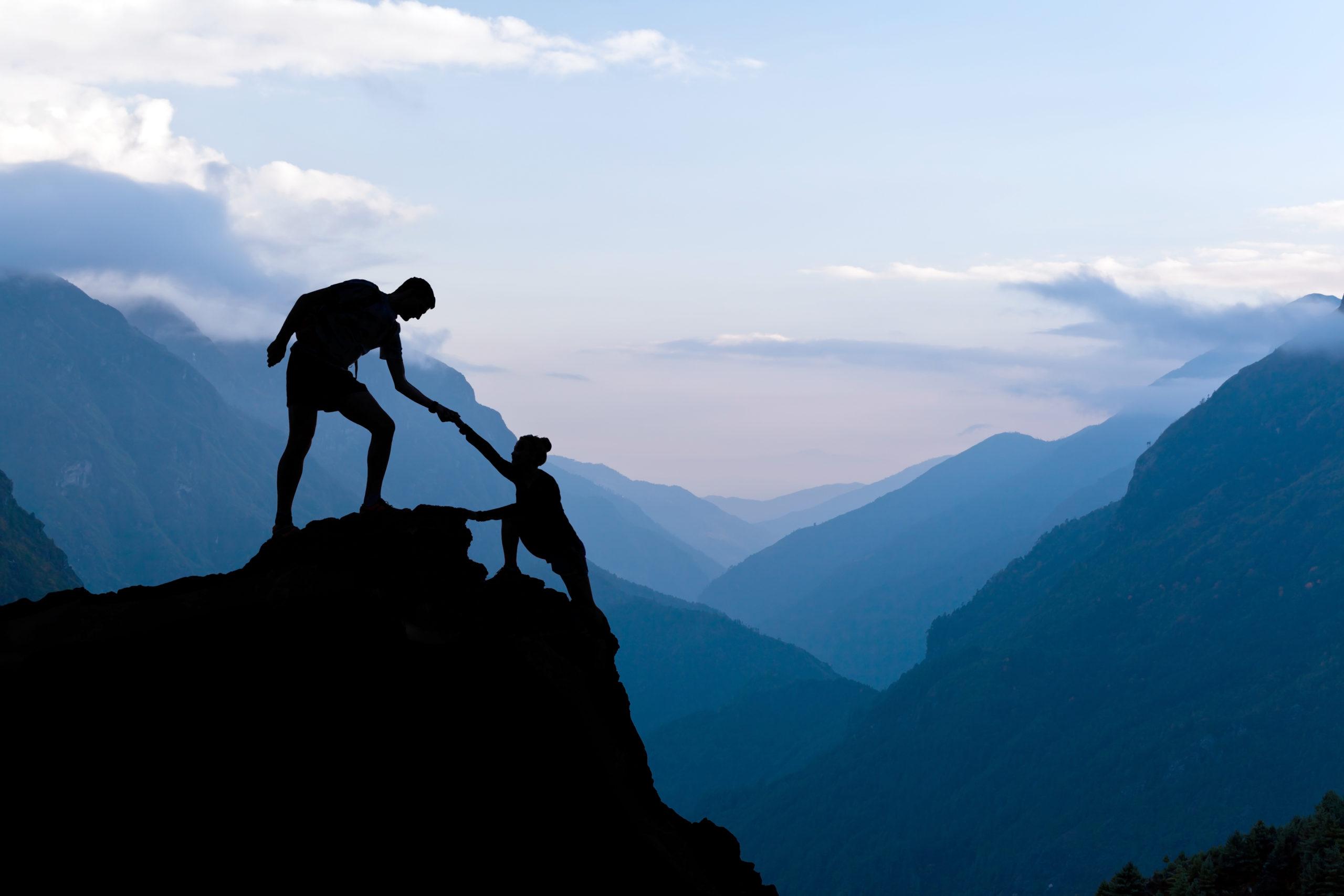 Mann hilft Frau auf Berg Silhouette Berge