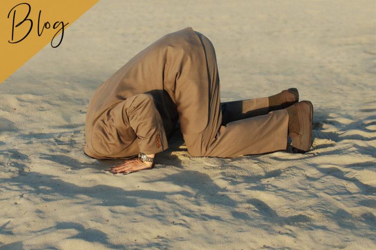 Mann streckt Kopf in den Sand