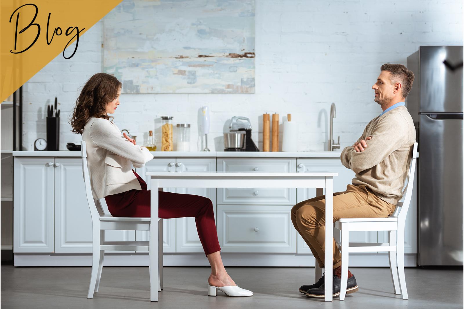 Paar sitzt sich mit verschränkten Armen gegenüber